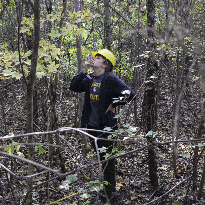 A student stands in a forest and measures the height of a tree with a clinometer.