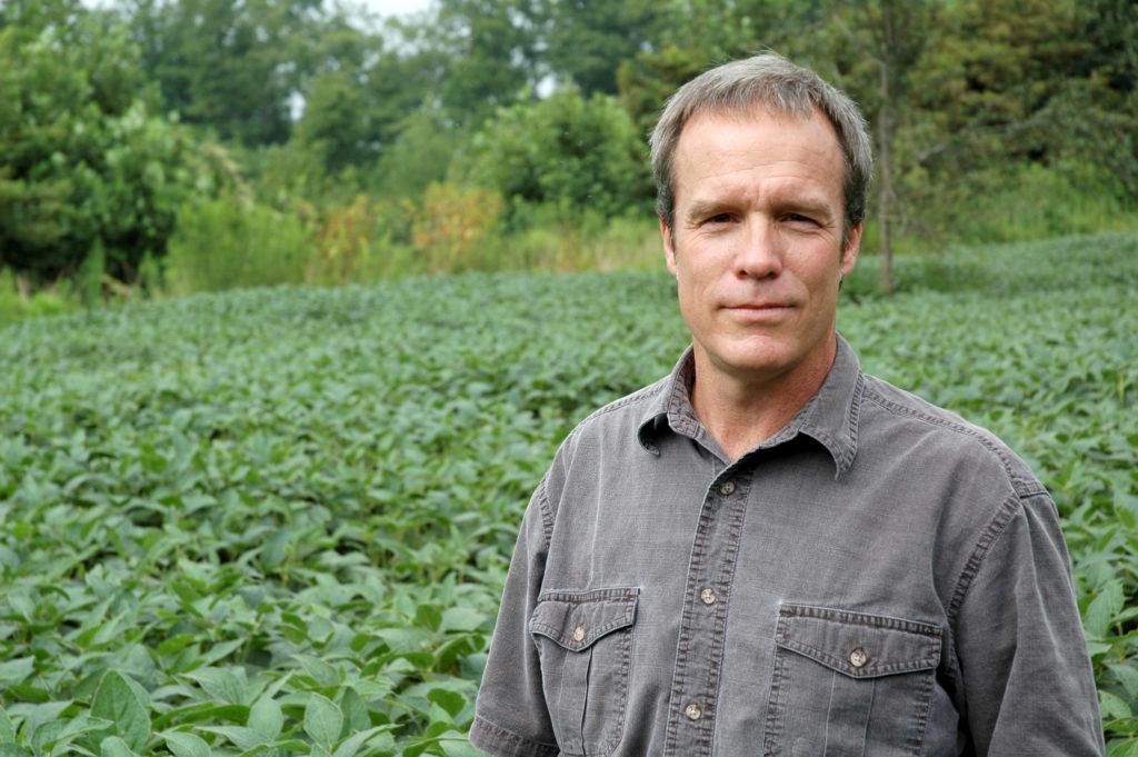 Professor Craig Harper stands in a food plot for deer.